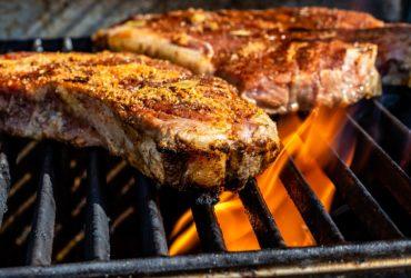 tva-kottbitar-som-ligger-pa-en-brinnande-grill-med-tjocka-grillgaller
