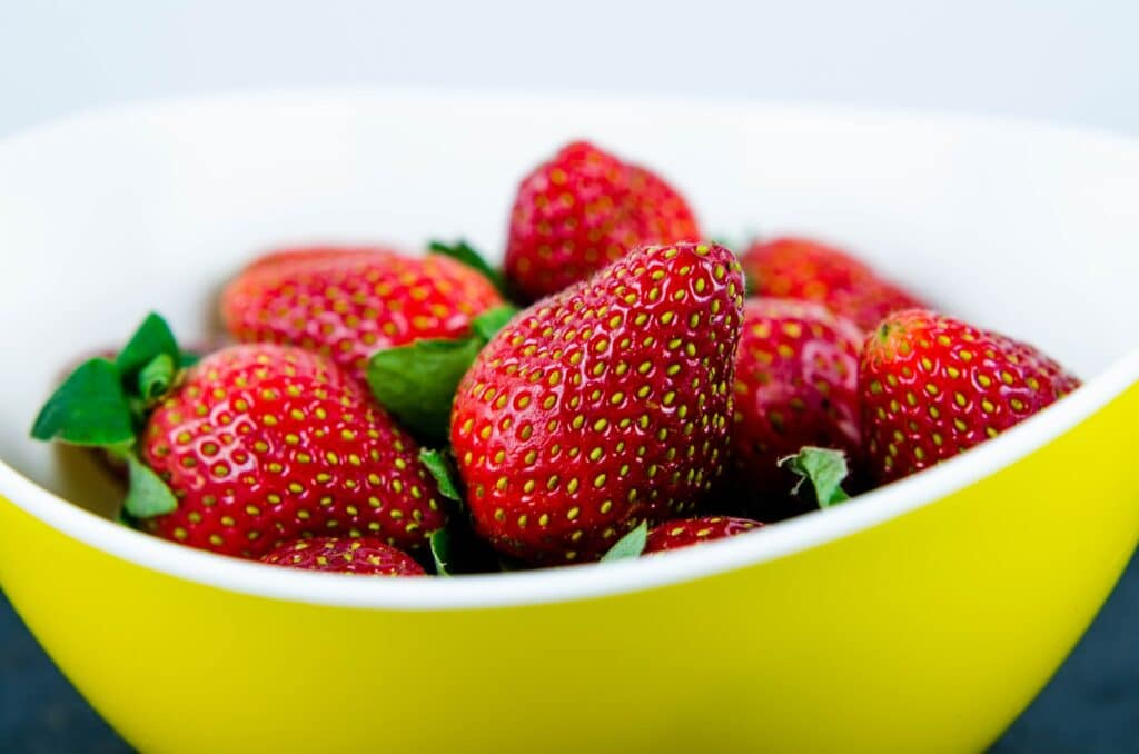 jordgubbar-med-gulfargade-fron-som-ligger-i-en-gul-skal